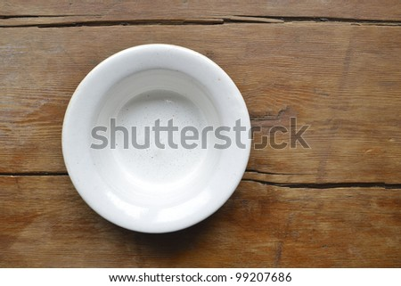white ceramic bowl on the vintage wooden table - stock photo
