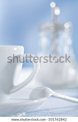 white ceramic coffee cup and spoon and sugar bowl - stock photo