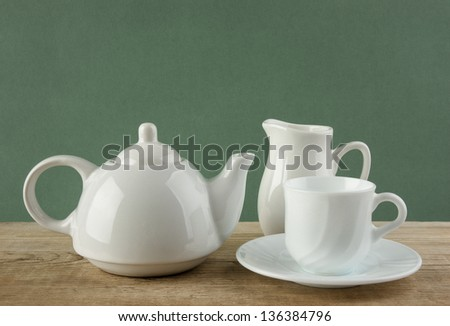white ceramic coffee set on old wooden table over green background