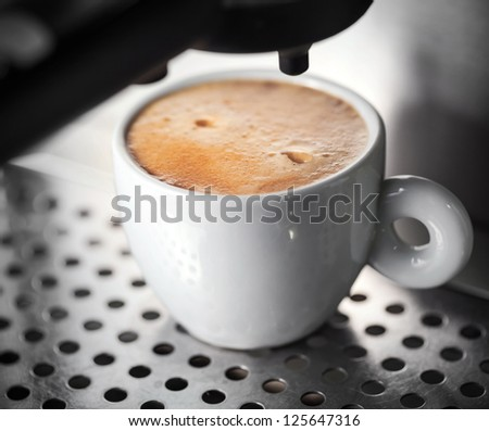 White ceramic cup of fresh espresso with foam in the coffee machine - stock photo