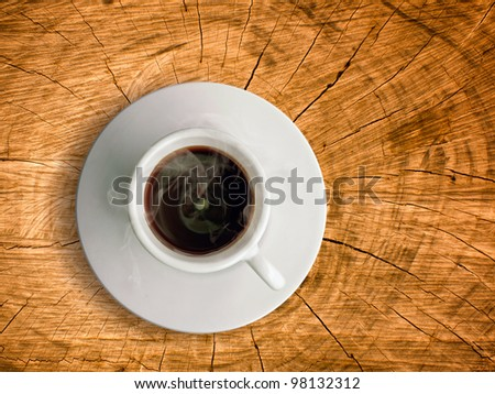White ceramic cup of hot coffee on old wood table