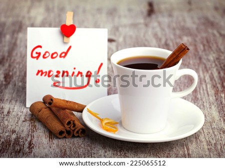white ceramic cup with coffee, saucer, cinnamon sticks and note on white paper on old wooden surface - stock photo