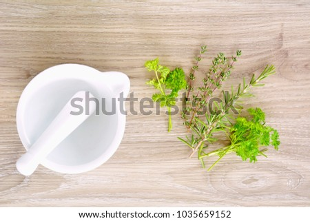 White ceramic mortar and pestle with fresh herbs in flat lay format and shot in natural light