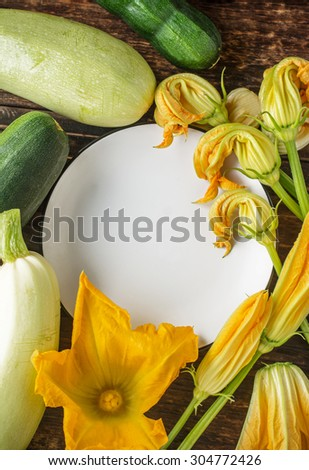 White ceramic plate surrounded by fresh flowers and colorful fruits of zucchini. Top view. selective Focus - stock photo