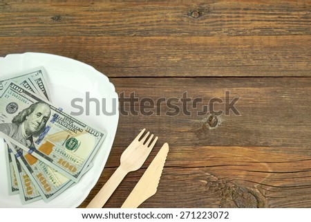 White Ceramic Plate With USA New One Hundred Dollar Bills, Wooden Fork And Knife On Rough Wood Background Or Texture With Copy Space - stock photo