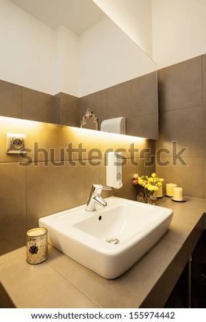 White ceramic sink on grey countertop in modern bathroom - stock photo