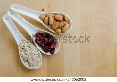 White ceramic spoons hold healthy foods of oats, dried cranberries, and almonds - stock photo