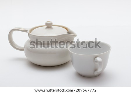 White ceramic tea pot with cup isolated on white.