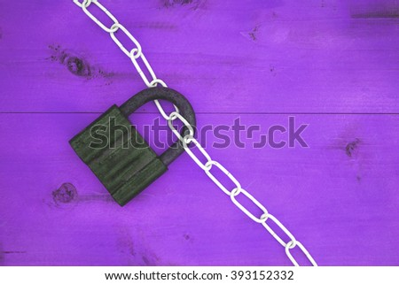 white chain and lock on a wooden surface purple - stock photo