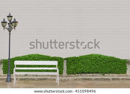 white chair and black electric light lamp post at Green Bushes fences at white brick wall  and concrete floor at walk way  - stock photo