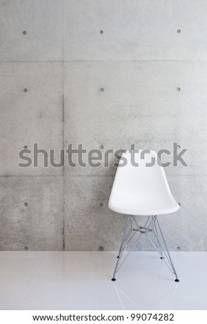 white chair and concrete wall - stock photo