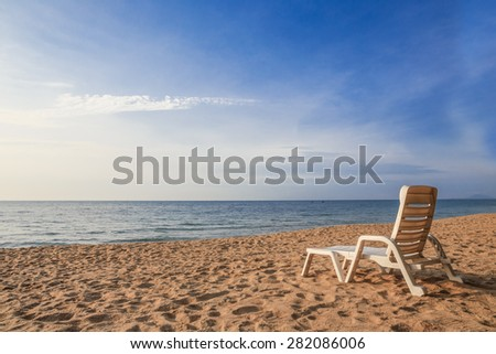 white chair on sand beach with sunshine light