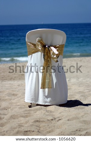 White chair with gold ribbon for a beach wedding - stock photo