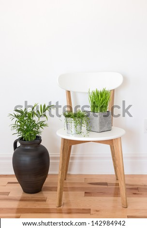 white chair with green plants in a room. - stock photo