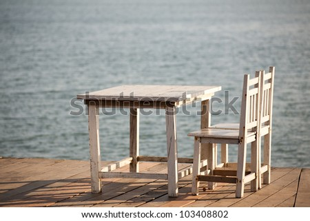 White chairs and table on a balcony with nice view to the sea. - stock photo