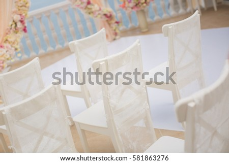 White chairs closeup on background of wedding arches peach color with flowers on the background of the sea.