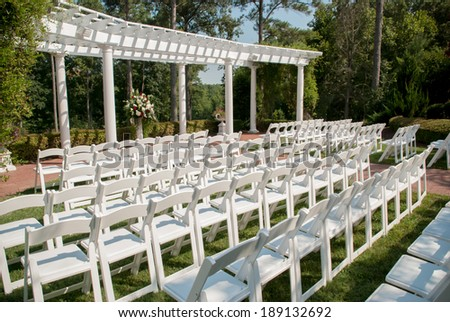 White chairs lined up for an outdoor wedding - stock photo