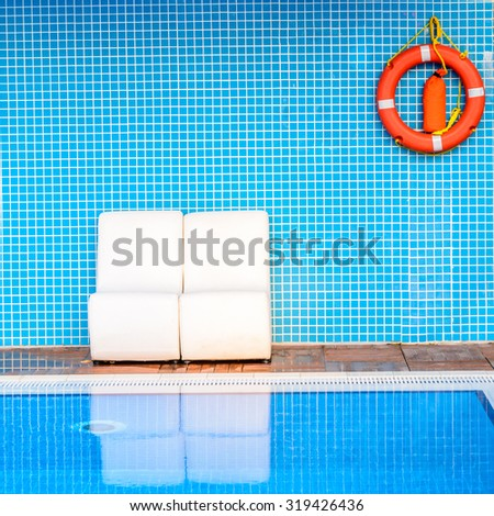 White chairs on blue background with an orange life buoy near swimming pool