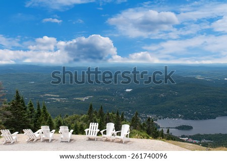 White chairs on top of mountain  at a ski resort during summer time depicting relaxing concept - stock photo