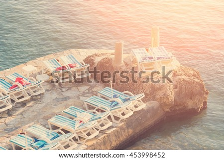 White chaise lounges on the stone platform by the sea. Toned - stock photo