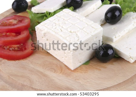white cheese with olives and tomato on wood