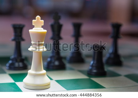 White chess king alone surrounded by the opposite pieces, selective focus on white chess king piece