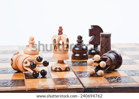 White Chess King between fallen queens win the game, surrounded by pawn, knight and rook, on old wooden chessboard,  - stock photo