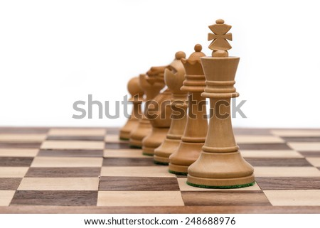 White chess pieces in a row (focus on king, background blurred) - stock photo
