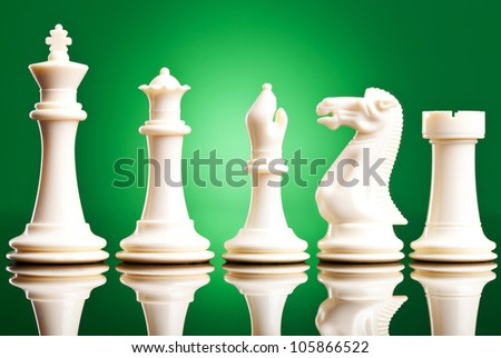 white chess pieces in order of decreasing importance, on green background
