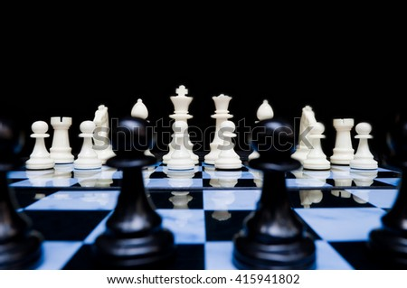 White chess pieces in set up position viewed from back line of black. Worm view as if in the eye of a black piece looking at the threatening white army. - stock photo