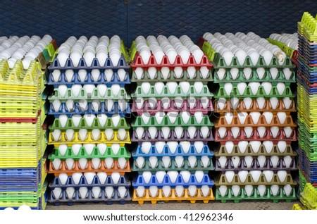 white chicken eggs in multicolored plastic boxes, India - stock photo