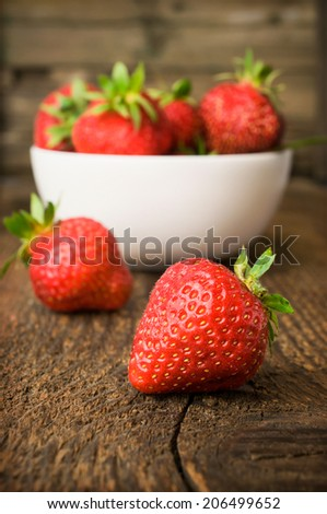 white china bowl filled with succulent fresh ripe red strawberries on an old wooden textured table top  - stock photo