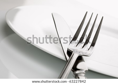 White china plate with crossed silver knife and fork cutlery, shallow deep of field - stock photo