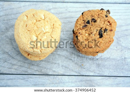 white chocolate chip cookies in a pile with oatmeal raisin cookies in pile on  a gray wooden background/white chocolate chip cookies/pile of white chocolate cookies - stock photo