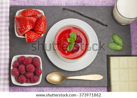 White chocolate panna cotta with raspberries and strawberries on a slate plate with ingredients and a white and purple napkin - stock photo