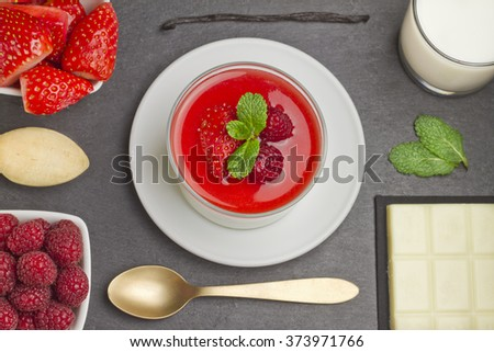 White chocolate panna cotta with raspberries and strawberries on a slate plate with ingredientsand a golden spoon - stock photo