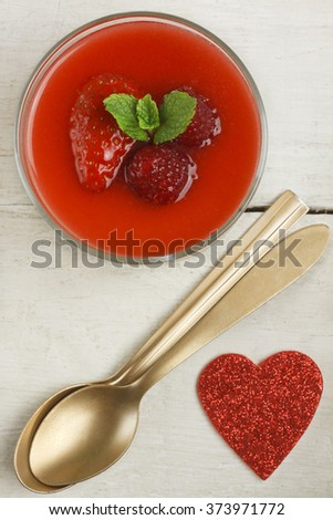White chocolate panna cotta with raspberries and strawberries, two golden spoons and red heart on white background - stock photo