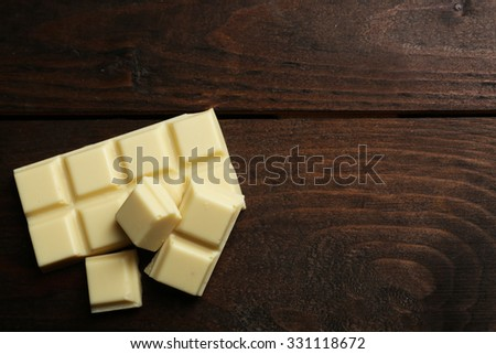 White chocolate pieces on wooden background - stock photo