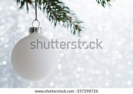 White christmas ball on the xmas tree on glitter bokeh background. Merry christmas card. Winter holidays. Xmas theme. Happy New Year. - stock photo