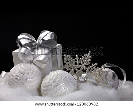 White Christmas balls, gift, snowflake - still life on black background