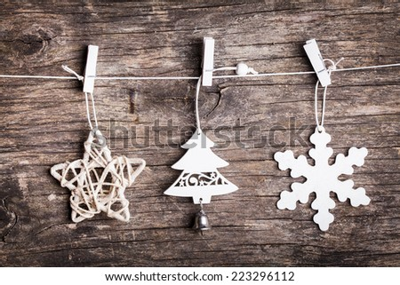 White christmas decorations attached to the rope, over wooden background - stock photo