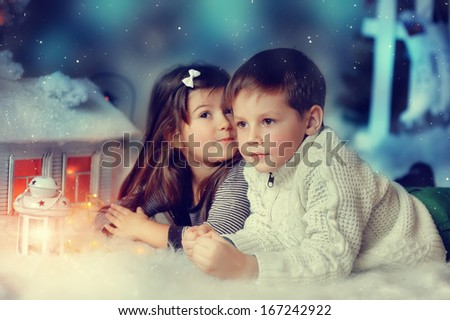 White Christmas fairy house with lights and cute little boy and girl - stock photo
