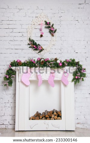 White Christmas fireplace decorated with fur tree, baubles and socks. Against white bright wall backgroud. Copy space - stock photo