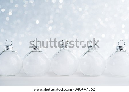 White christmas ornaments on glitter bokeh background with space for text. Merry christmas card. Winter holidays. Xmas theme. Happy New Year. - stock photo