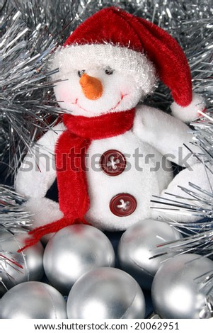 White Christmas snowman sitting in tinsel and other decorations