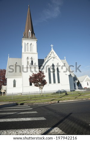White church, traditional architecture constructed in 1881 with pedestrian crossing in Cambridge, NZ. - stock photo