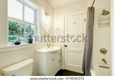 White clean bathroom interior. Small vanity cabinet with a sink, grey shower curtain and a window. Northwest, USA