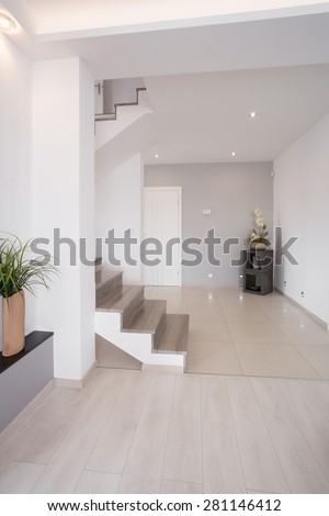 White clean hallway with wooden stairs on the first floor - stock photo