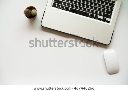 White clean office desk with laptop, notebook and cactus. Top view with copy space.