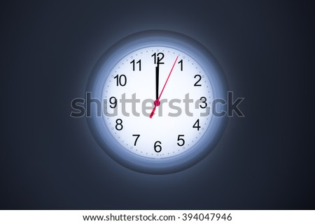 white clock at midnight time with dark color tone style background / glow in the dark room clock / work hard and late night background /insomnia clock / night shift work clock - stock photo